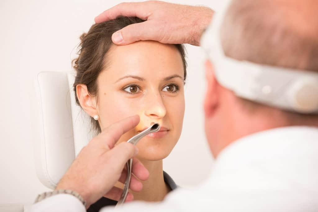 HNO-Arzt untersucht Nase einer Patientin