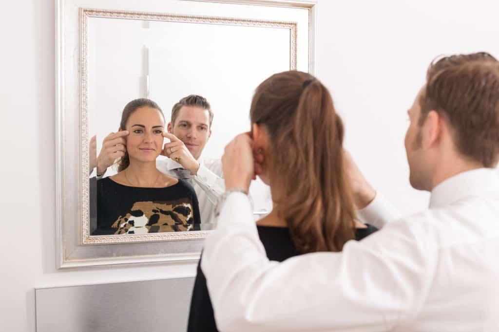 Schönheitschirurg mit Patientin vor Spiegel