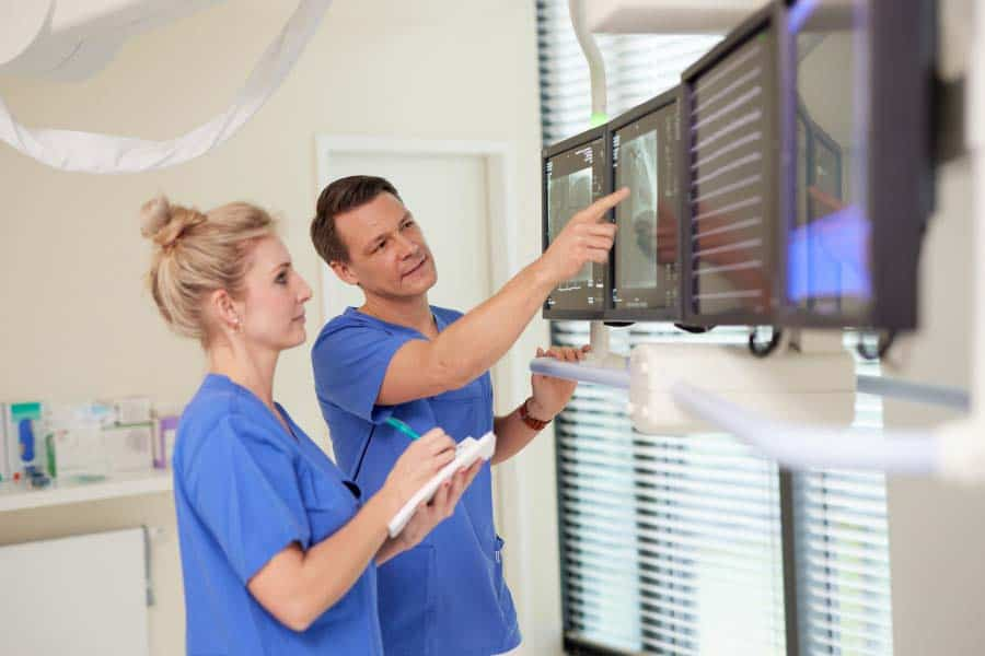 Dr. Hausen und Assistentin vor Monitoren bei Herzkatheteruntersuchung