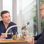 Prof. Dr. Thomas Gasser erklärt dem Patienten die Tiefe Hirnstiumulation und die Geräte genau.