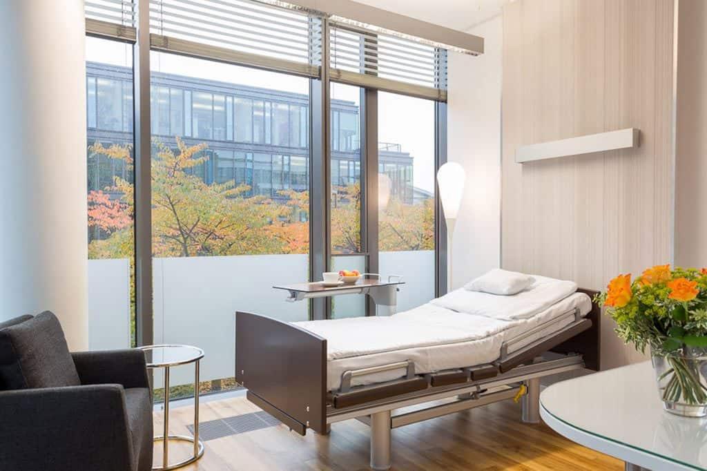 Modernes Patientenzimmer mit einem Bett und großem Fenster