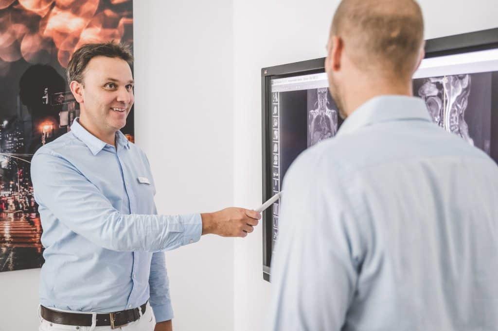 Dr. Demant erklärt Patienten etwas am Fernseher