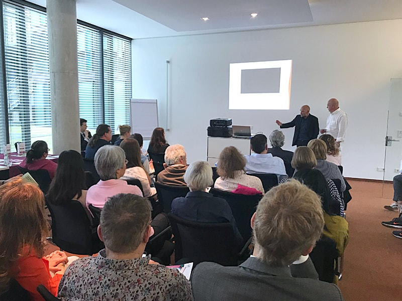 Dr. med. Christoph Grothe (oben rechts im dunklen Jacket) der GFO Kliniken Troisdorf und Prof. Dr. med. Christian E. Elger (oben rechts im weißen Hemd) im Gespräch mit den Medizinerinnen und Medizinern der Fortbildung.