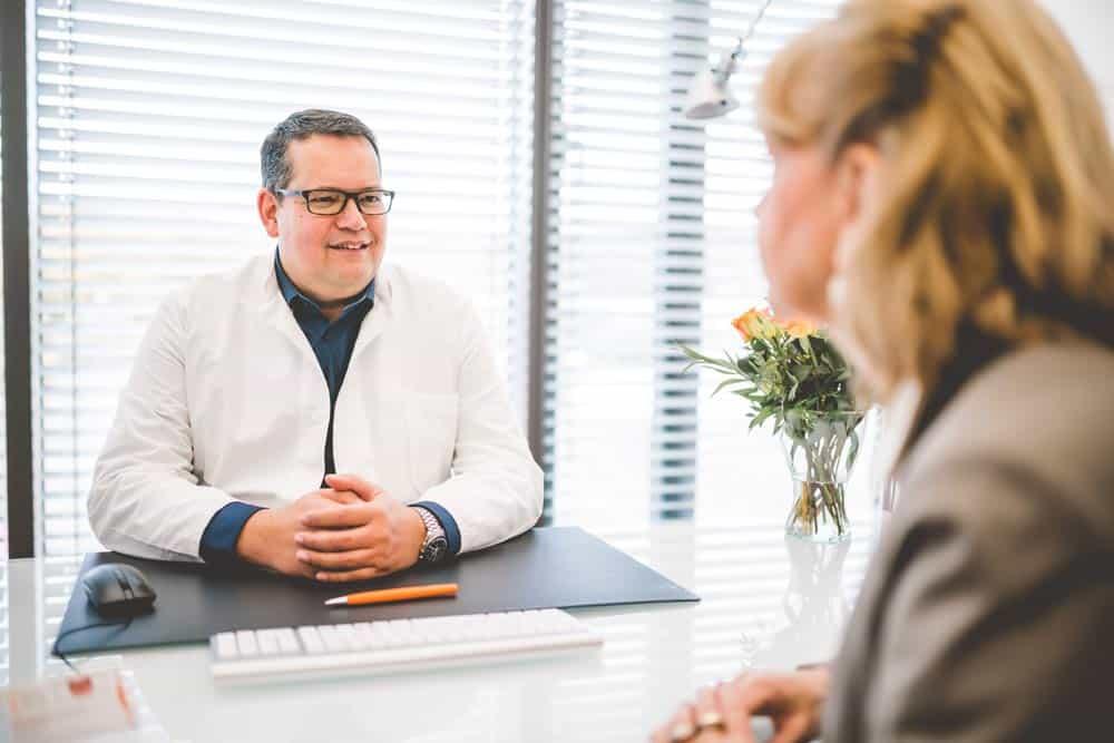 Stefan Mühlbauer im Patientengespräch am Tisch