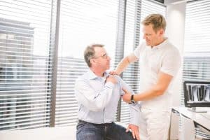 Dr. Springorum fühlt Schulter von Patient